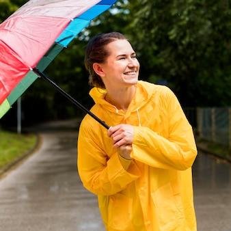 Frau im regenmantel lächelnd