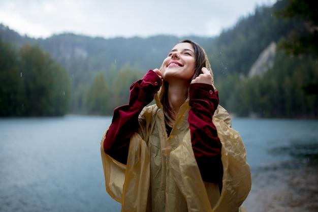 Frau im regenmantel nahe see am regnerischen tag.