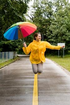 Frau im regenmantel springend, während sie ihren regenschirm hält