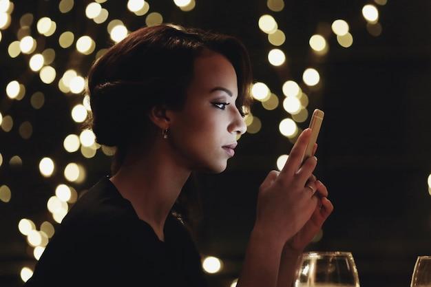 Frau im restaurant mit dem smartphone