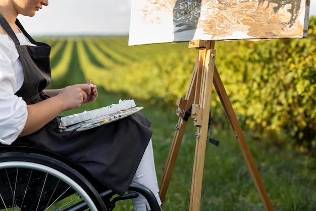Frau im rollstuhl, der draußen in der natur malt