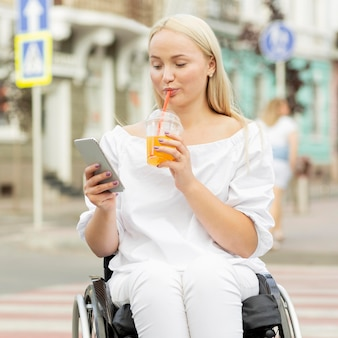 Frau im rollstuhl, die ein getränk hat und smartphone verwendet