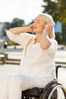 Frau im rollstuhl, die musik auf kopfhörern draußen genießt