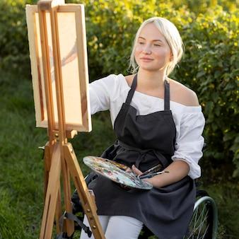 Frau im rollstuhl draußen in der natur mit leinwand und palette