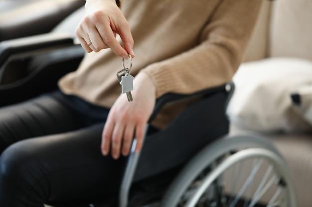 Frau im rollstuhl hält schlüssel zur wohnung
