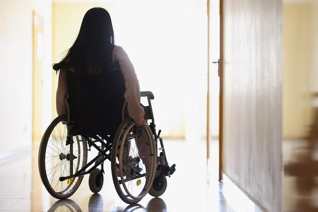 Frau im rollstuhl im dunklen flur schaut aus dem fenster
