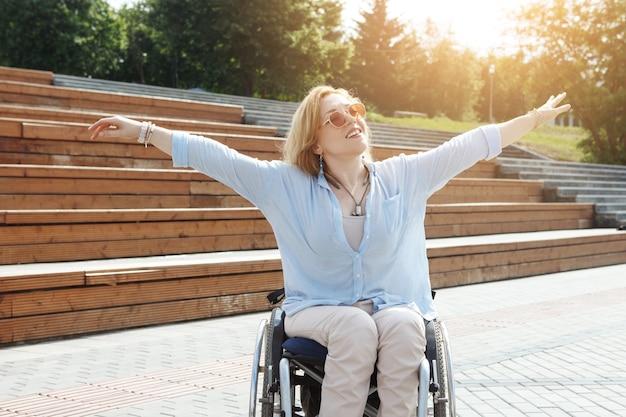 Frau im rollstuhl im stadtpark. das konzept einer zugänglichen umgebung für behinderte menschen.