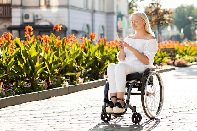 Frau im rollstuhl in der stadt, die smartphone mit kopienraum verwendet