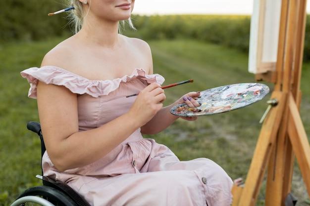Frau im rollstuhl mit leinwand und palettenmalerei außerhalb
