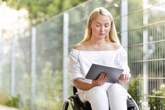 Frau im rollstuhl mit tablette