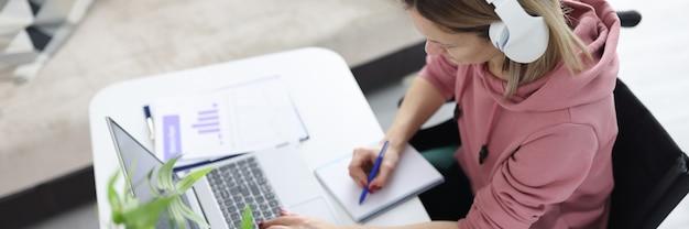 Frau im rollstuhl sitzt am schreibtisch mit kopfhörern und macht sich notizen in der notebook-fernbedienung