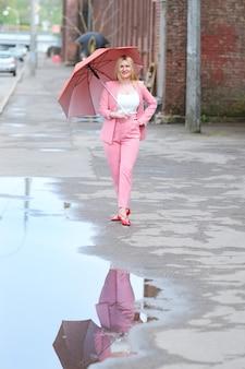 Frau im rosa anzug mit regenschirm gehend auf die straße nach dem regen