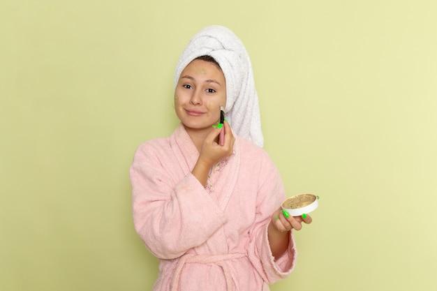 Frau im rosa bademantel beim schminken