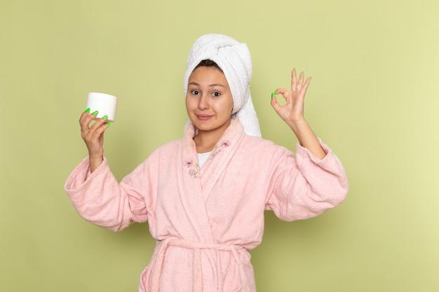 Frau im rosa bademantel, der creme für gesicht hält