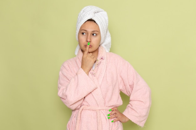 Frau im rosa bademantel, der mit denkendem ausdruck aufwirft