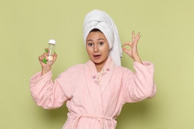 Frau im rosa bademantel, der sprühflasche hält