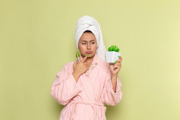 Frau im rosa bademantel, der sprühflasche und pflanze hält