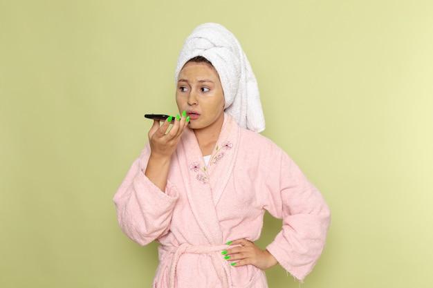 Frau im rosa bademantel, die eine sprachnachricht sendet