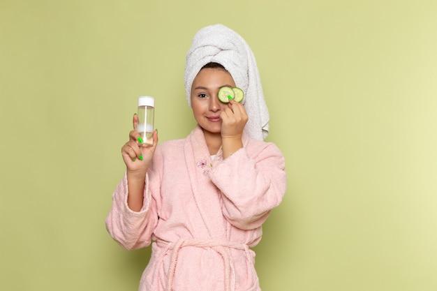 Frau im rosa bademantel hält sprühflasche und gurkenringe