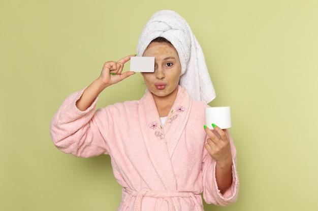 Frau im rosa bademantel hält weiße karte und creme