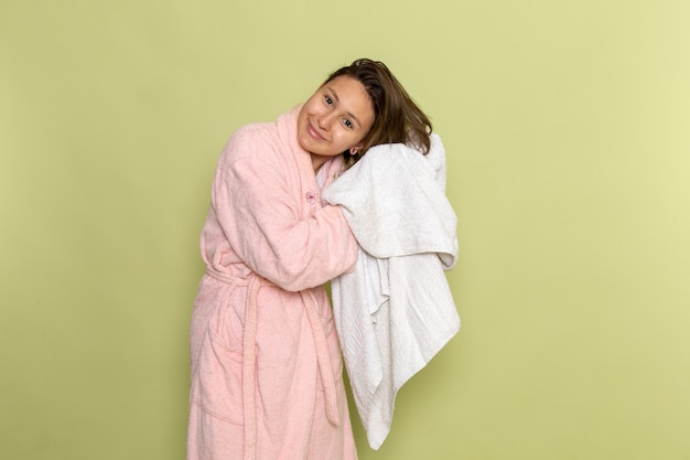 Frau im rosa bademantel lächelt und trocknet ihre haare