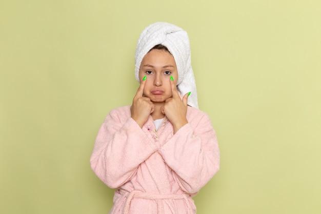 Frau im rosa bademantel posiert mit traurigem ausdruck