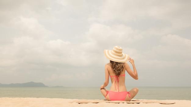 Frau im rosa bikini mit dem sonnenhut, der am strand im sommer sitzt