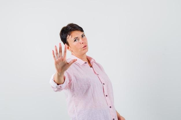 Frau im rosa hemd, das stoppgeste zeigt und ernsthafte vorderansicht sieht.