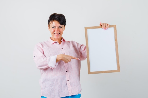 Frau im rosa hemd, hose zeigt auf leeren rahmen und schaut fröhlich, vorderansicht.