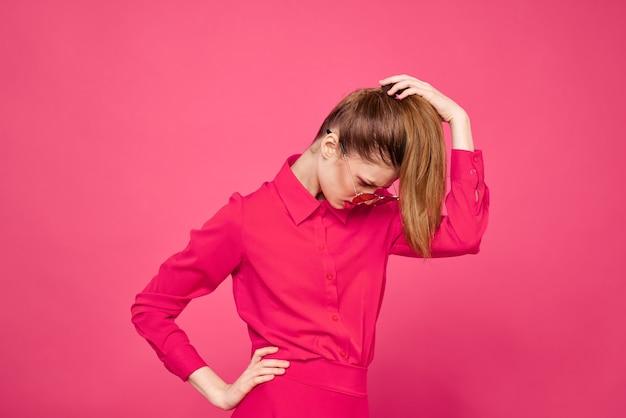 Frau im rosa hemd und in den braunen gläsern beschnittenen ansichtsmodemotionsgefühle, die hände porträt gestikulieren.