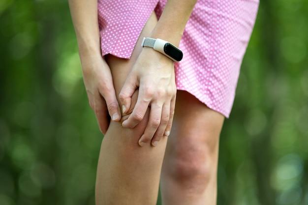 Frau im rosa kleid, das ihr knie mit den händen hält, die krampfschmerzen haben.