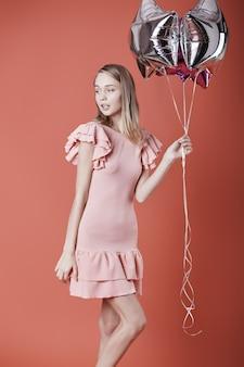 Frau im rosa kleid, das luftballons hält.