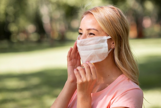 Frau im rosa t-shirt, das medizinische maske im park trägt