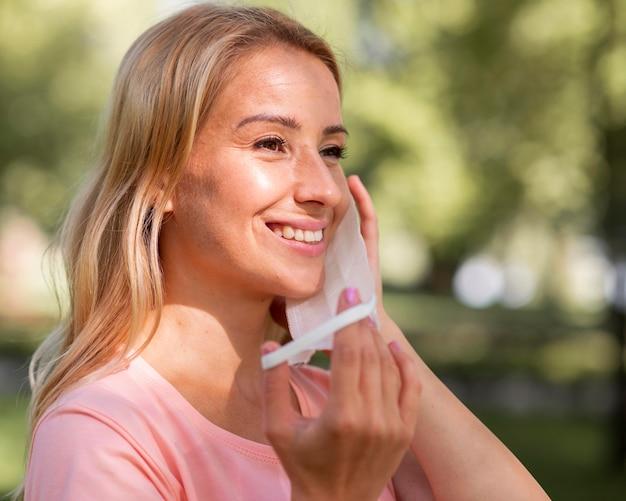 Frau im rosa t-shirt unter verwendung einer medizinischen maske