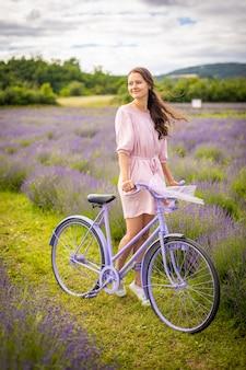 Frau im rosafarbenen kleid mit retro-fahrrad im lavendelfeld tschechien