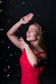 Frau im rosafarbenen tanzen unter glänzenden flitter