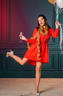 Frau im rot mit champagnerglas