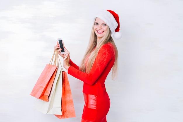 Frau im rot mit einkaufstaschen und telefon Kostenlose Fotos