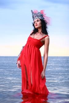 Frau im roten avantgardekleid am strand im wasser