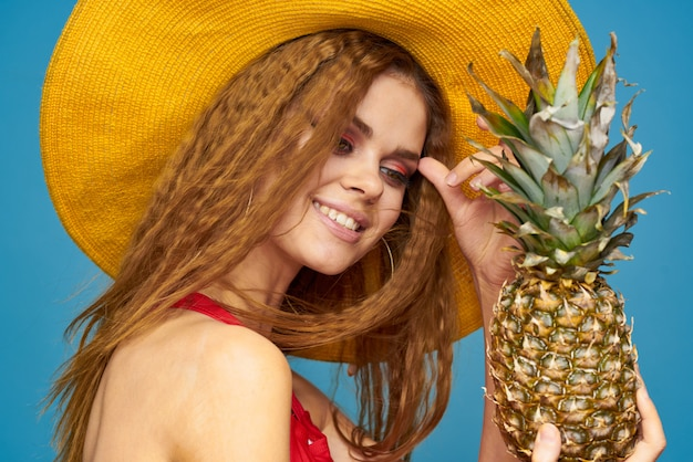 Frau im roten badeanzug und im gelben hut, der im studio ein heißes tropisches bild mit ananas aufwirft