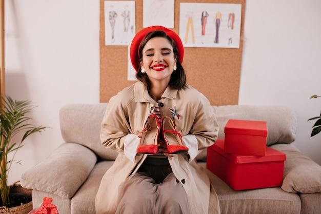 Frau im roten hellen hut und im beigen graben hält ihre lieblingsschuhe. charmante freudige dame in stilvollen kleidern, die für kamera aufwerfen.