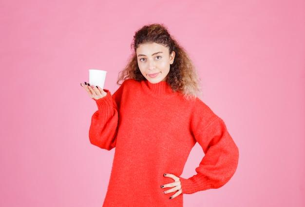 Frau im roten hemd, das eine wegwerfkaffeetasse hält.