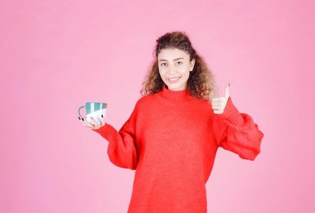 Frau im roten hemd, die eine kaffeetasse hält und den geschmack genießt.