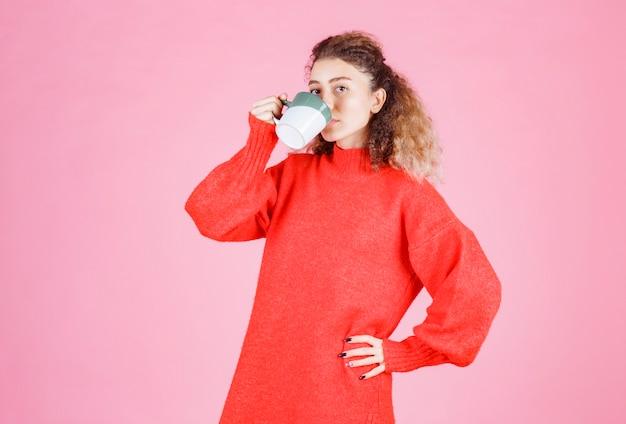 Frau im roten hemd, die eine tasse kaffee trinkt.