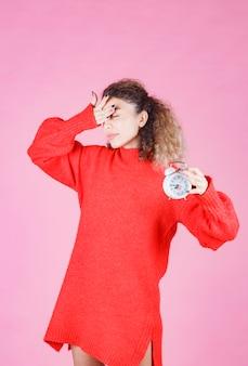 Frau im roten hemd mit wecker und sieht schläfrig aus.
