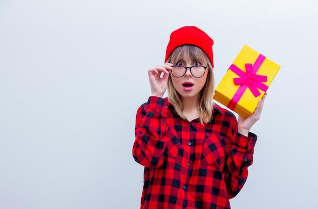Frau im roten hemd und hut, die feriengeschenkbox hält