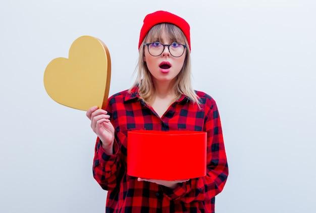 Frau im roten hemd und im hut, die herzformgeschenkbox hält