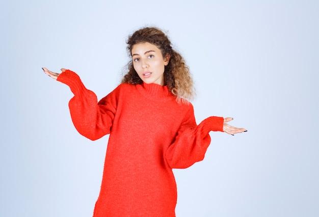 Frau im roten hemd weit öffnet ihre hand und sieht verwirrt aus.