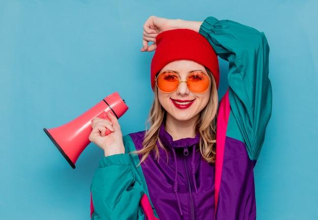 Frau im roten hut, sonnenbrille und anzug der 90er jahre mit lautsprecher