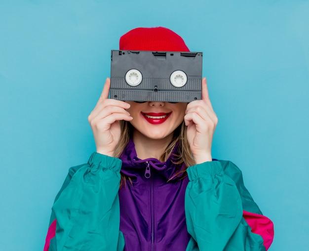 Frau im roten hut, sonnenbrille und anzug der 90er jahre mit vhs-kassette